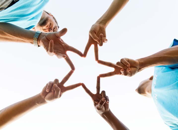 Un groupe de personnes forment une étoile en joignant leurs doigts