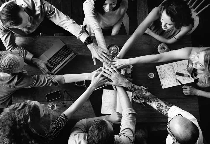 Un groupe de personnes rejoignent leurs mains au centre de la table en guise de lien et de soutien