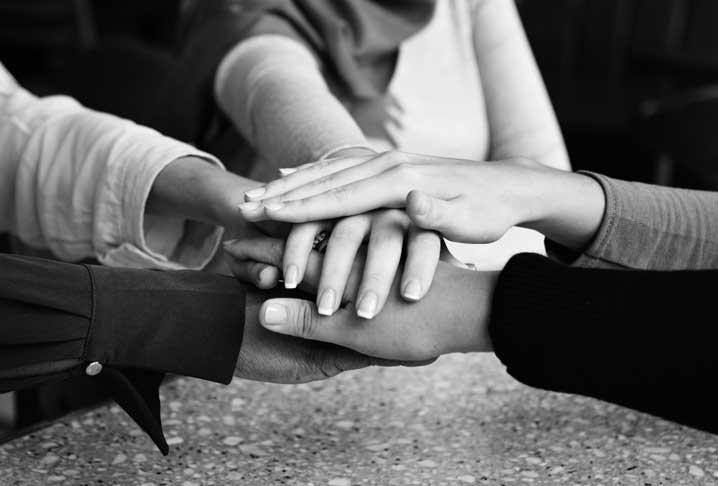 Des mains se joignent au centre en guise de soutien
