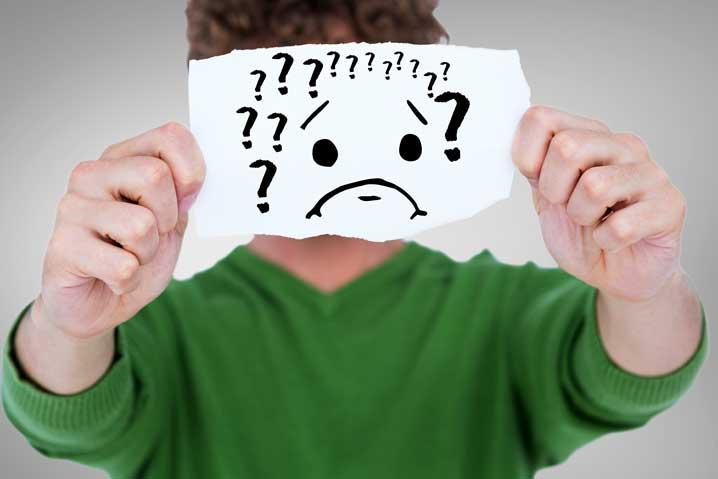 Un homme tient un papier devant son visage sur lequel est dessiné un émoticon triste et des points d'interrogation